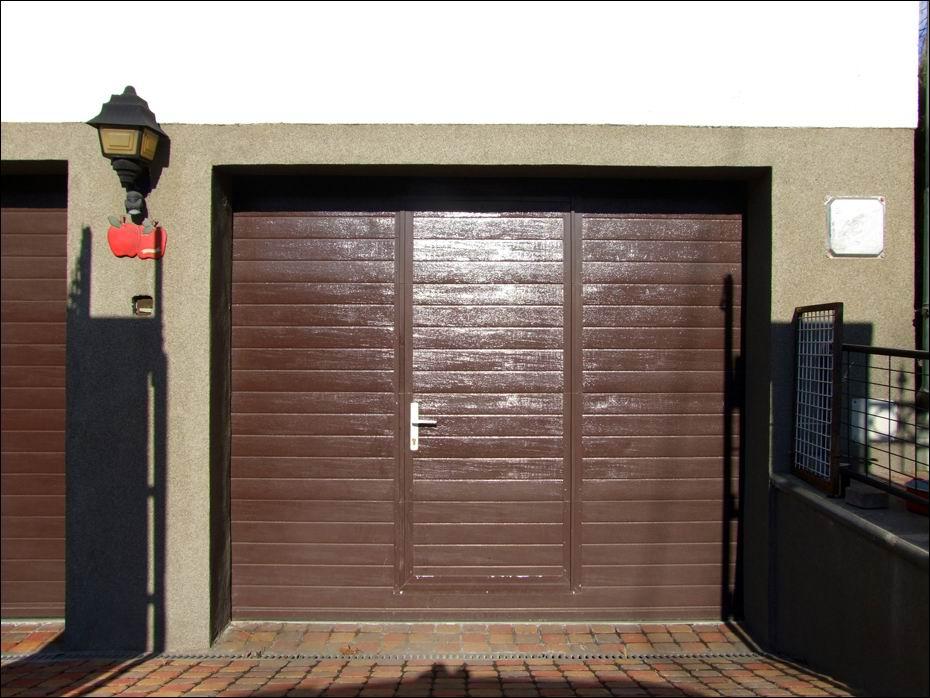 Hőszigetelt, szekcionált, barna garázskapu beépített ajtóval, elegáns bordás mintázattal, szemből fotózva