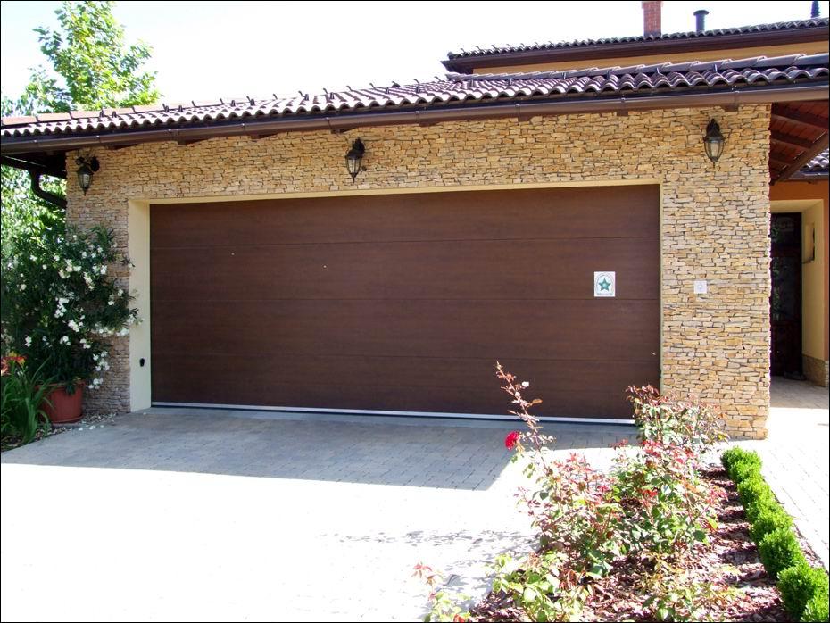 A hőszigetelt, ECOTOR típusú, dió fadekor garázskapu, széles bordás mintázattal, harmonikusan illeszkedik az épülethez