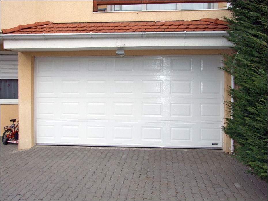 Fehér szinű, kazettás mintázatú, szekcionált, hőszigetelt garázsajtó Sasvári Sándor csömöri otthonában