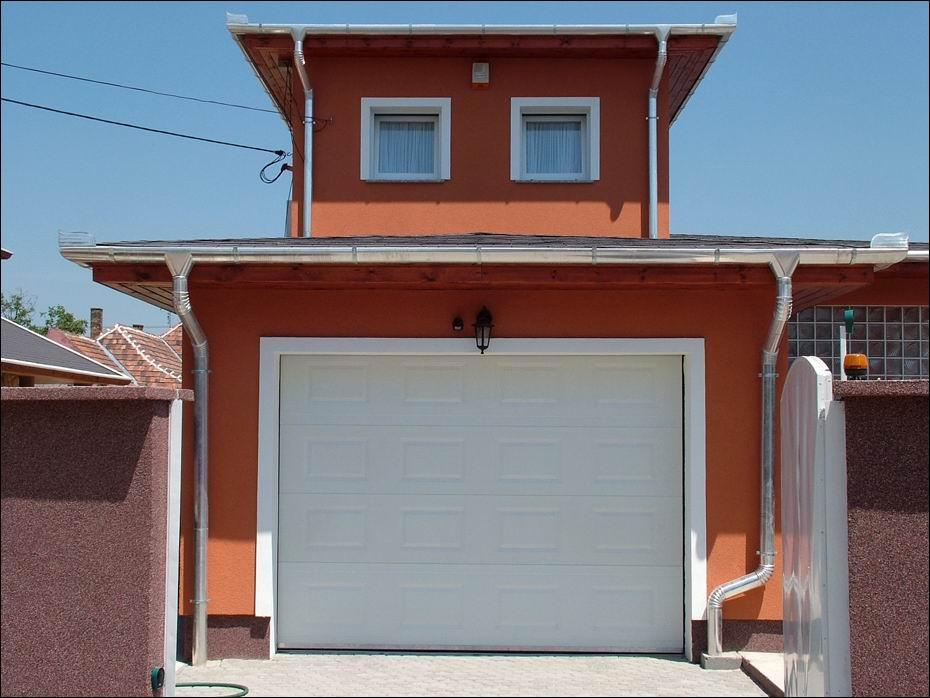 Taksony, Vezér utca: kazettás mintázatú, fehér színű, hőszigetelt, szekcionált garázskapu szemből